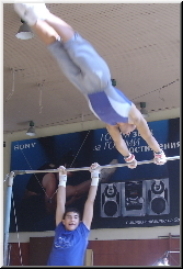 2 gymnasts doing giants on the high bar at the same time